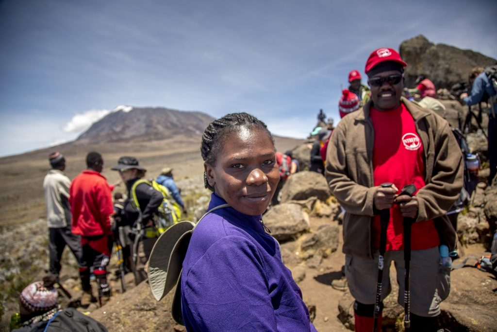 Eva Mageni Daudi, Tanzanian woman farmer and President of the Rural Women's Farmers forum, stands stands atop Zebra Rock, 4,000 meters up Mount Kilimanjaro.