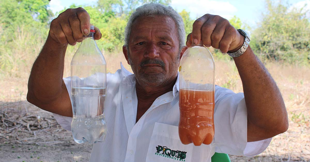 A villager in northeastern Brazil holds two plastic bottles, one filled with waters polluted by agribusiness activity
