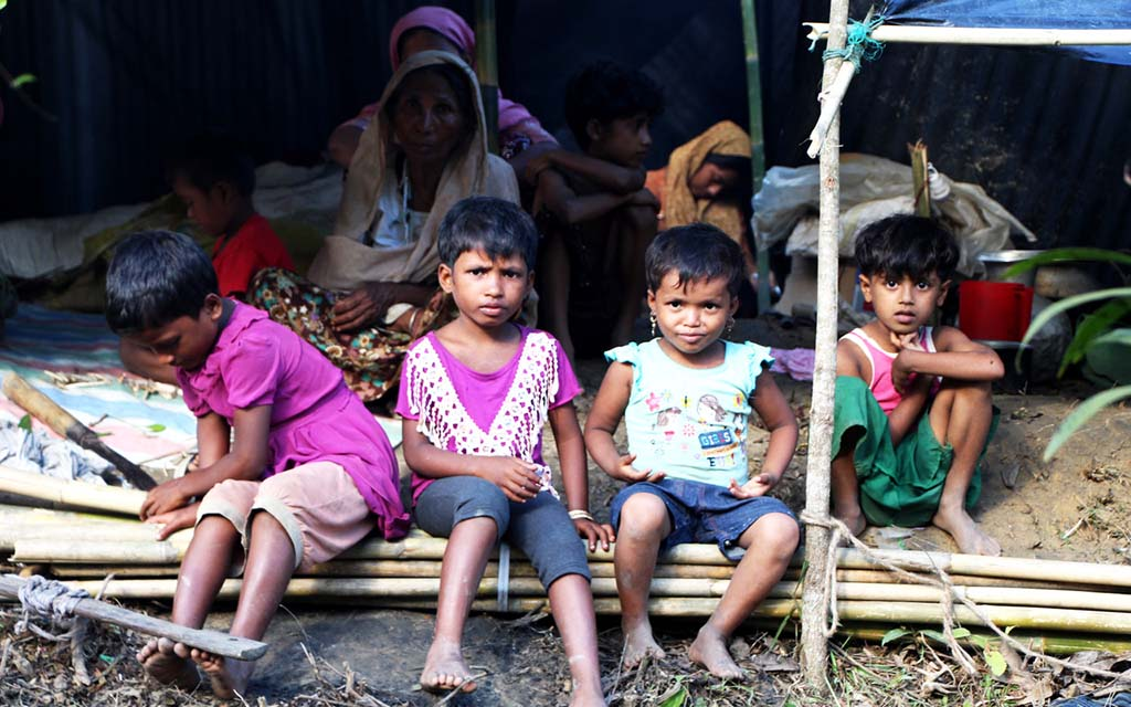 Four Rohingya children sit under a tent at a refugee camp in Bangladesh.