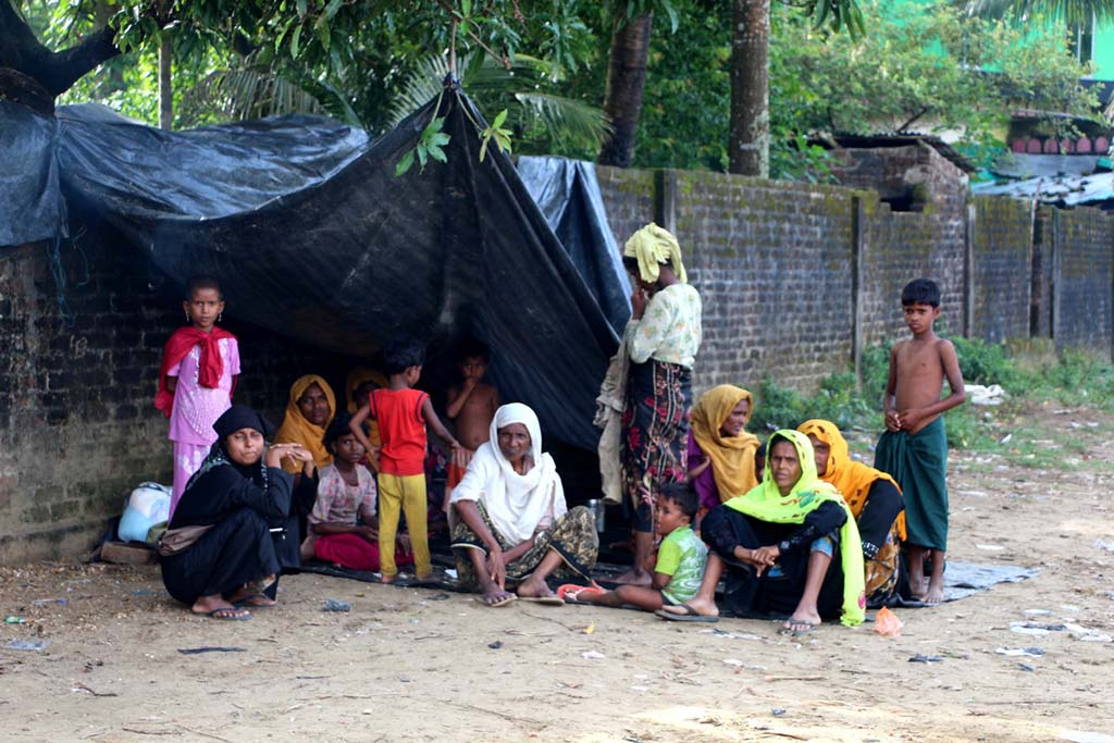 A group of women and children sit under a makeshift tent by the road.