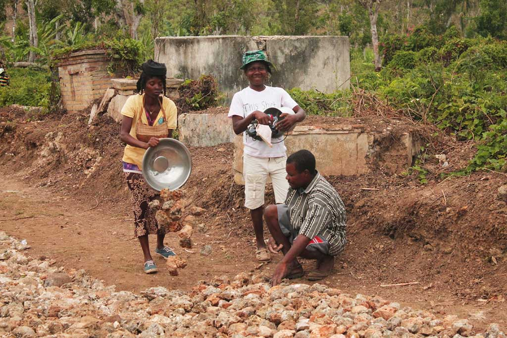 In Haiti, two women and a man place stones on the ground as they repair roads after Hurricane Matthew.