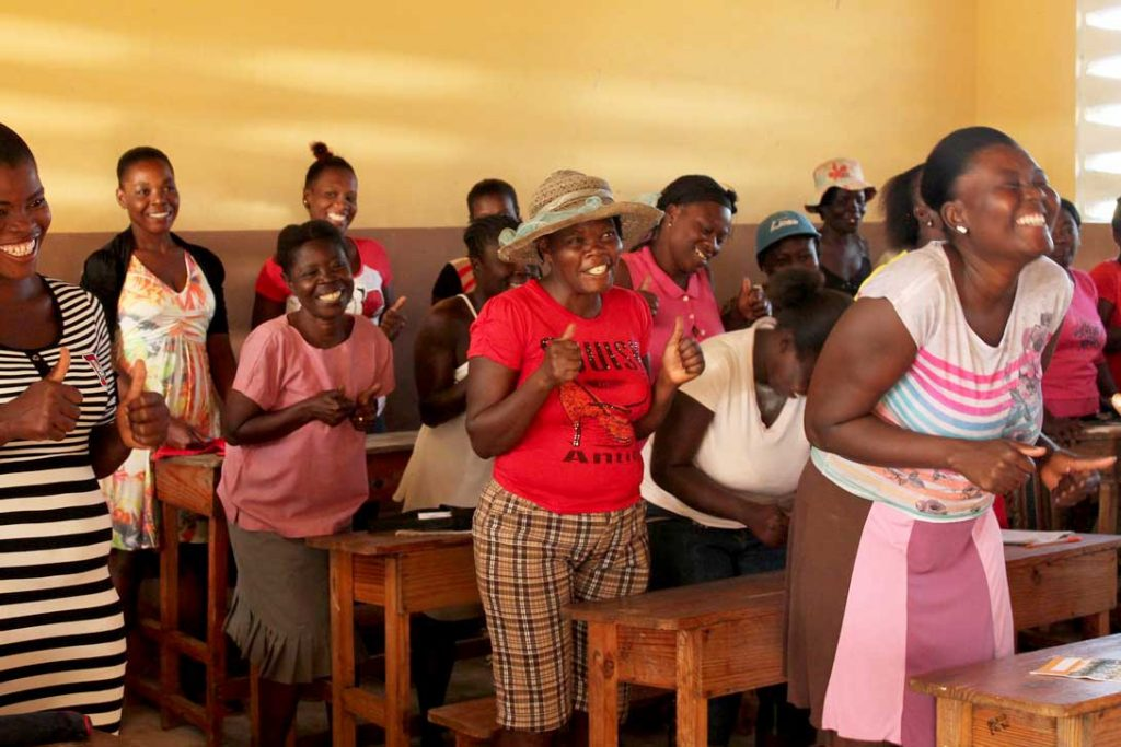 Women stand behind desks in rows with their thumbs up as part of a protection training in Haiti after Hurricane Matthew.