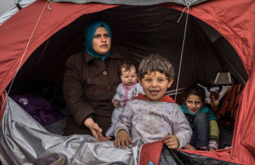 A Syrian refugee woman sits in a tent with her three children. Her young son is standing the foreground, smiling.