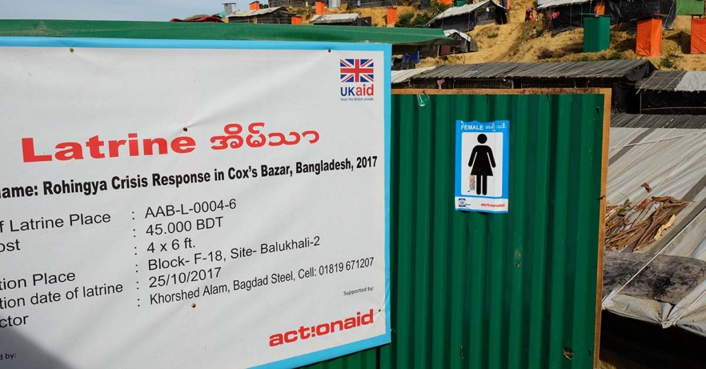 """A green structure with a large sign that reads: """"Latrine"""" and features ActionAid's logo. A sign next to it indicates that the bathroom is for female use. ActionAid Bangladesh built this to address concerns of safety among Rohingya women in the refugee camp."""