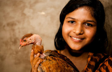 A portrait of a girl smiling and holding a chicken.
