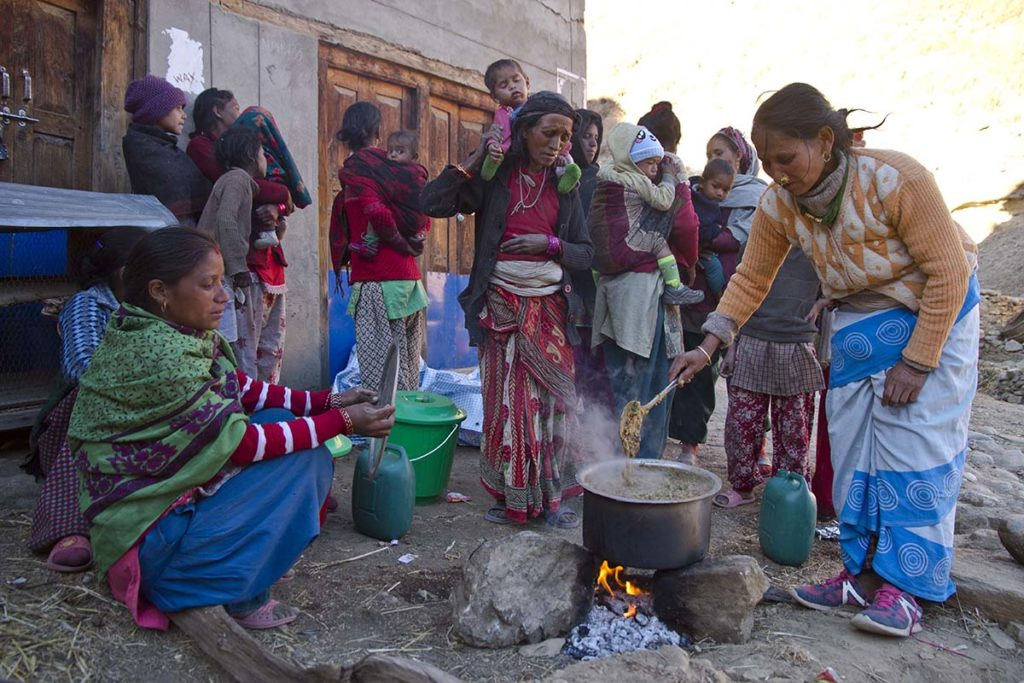 A group of women and children congregate around a large pot of stew cooking over rocks.