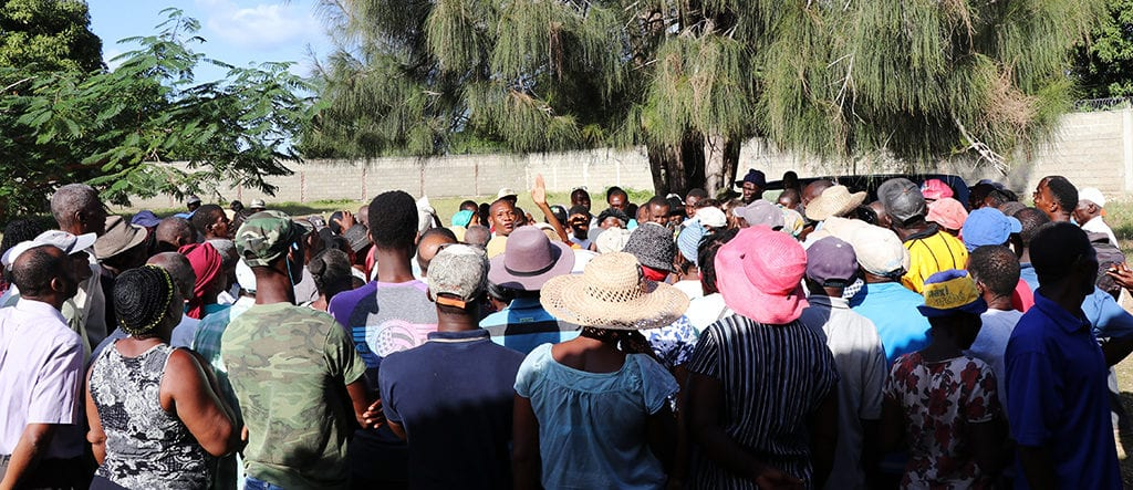 A group of Haitian farmers gather in an outdoor space to discuss the details of the final agreement.