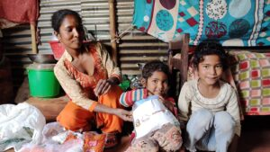 Anjana and her children receive a coronavirus prevention kit from ActionAid in Nepal.