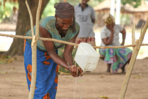 Ningo community member, Asibi, demonstrates how to set up the improvised tap that has been replicated in all households in her community