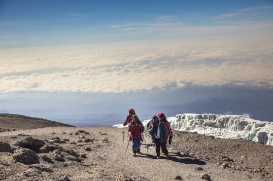 African women farmers stand atop Mt. Kilimanjaro, with the mountain's famous glacier on the left. Photo: Georgina Goodwin/ActionAid
