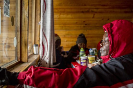 Polly, a farmer and women's rights activist from Uganda, gazes out from Horombo Hut, situated halfway up Kilimanjaro. Photo: Georgina Goodwin/ActionAid