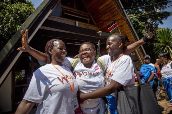 Suzy, farmer and women's rights activist from Kenya, greets fellow Kenyan women upon her descent from the mountain. Photo: Georgina Goodwin/ActionAid