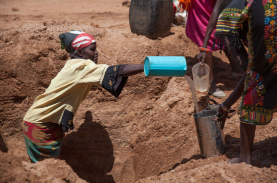 A woman standing in a ditch pours water into a bucket.