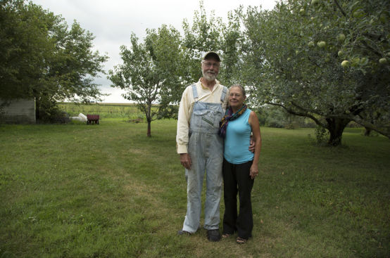 A man and a woman stand next to each other on a grassy field. The man, dressed in overalls, has his left arm around the woman.