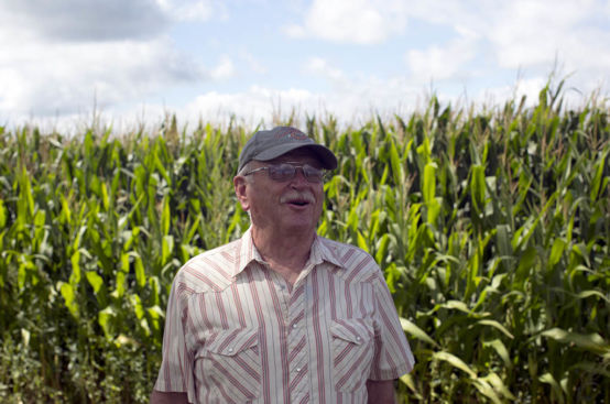 A man with a white mustache and a cap stands in front of cornstalks.