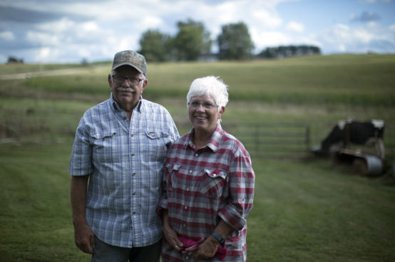 A man and a woman stand next to each other on a grassy field. Family farmers like them need a farm bill that supports their livelihood.